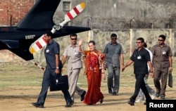 Chief of India's ruling Congress party Sonia Gandhi (C), surrounded by her security personnel, waves to her supporters after addressing an election campaign rally at Rae Bareli in Uttar Pradesh, Apr. 26, 2014.