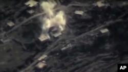 In this photo made from the footage with information taken from Russian Defense Ministry official website on Feb. 11, 2016, an aerial image shows an air strike on a militant base in the province of Latakia, Syria.