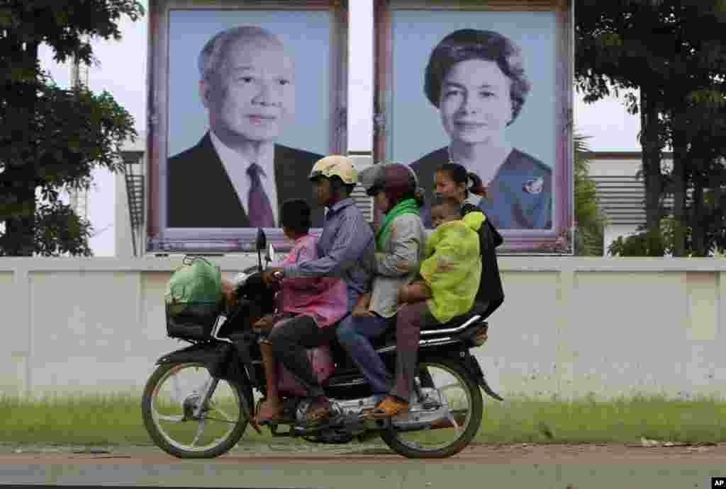 Cambodian family members ride on a motorbike as they head back from their home village, passing by portraits of former King Norodom Sihanouk, left, and his wife Queen Monineath, Phnom Penh, Cambodia, October 15, 2012.