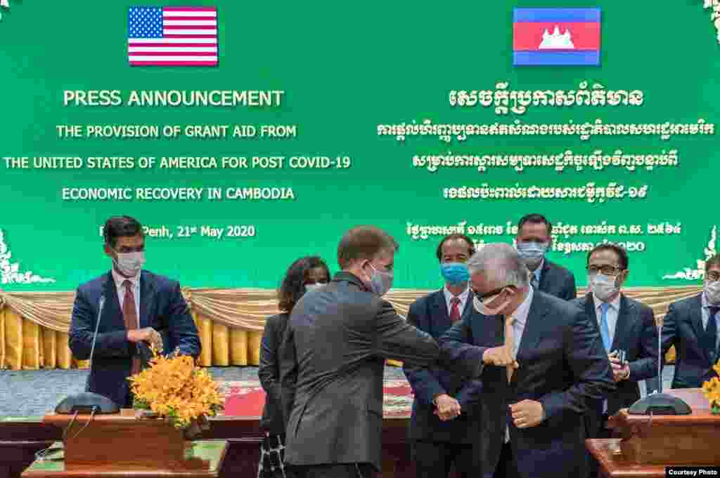 U.S. Ambassador W. Patrick Murphy elbow-greets Cambodian Minister of Economy and Finance, Aun Pornmoniroth, at an event announcing the U.S. assistance of $7.5 million, and a total of $11 million since the COVID-19 outbreak, supporting Cambodia's response
