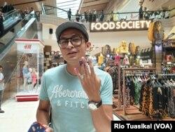 Pemilih di Jakarta asal Kediri, Ali Markus, menunjukkan jari ungu ketika akan berburu diskon Klingking Fun di pusat perbelanjaan Kota Kasablanka, Jakarta, Rabu, 17 April 2019.(Foto: Rio Tuasikal/VOA)