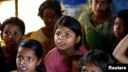 កុមារជនភៀសខ្លួនកំពុងផ្ទៀងស្តាប់គ្រូខណដែលពួកគេកំពុងរៀននៅក្នុងជំរំជនភៀសខ្លួន Balukhali ទីក្រុងCox's Bazar ប្រទេសបង់ក្លាដែស កាលពីថ្ងៃទី១០ ខែ មេសា ឆ្នាំ ២០១៧។