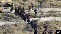 FILE - This Nov. 27, 2016 photo provided by the Rumaf, a Syrian Kurdish activist group, which has been authenticated based on its contents and other AP reporting, shows people fleeing rebel-held eastern neighborhoods of Aleppo into the Sheikh Maqsoud area that is controlled by Kurdish fighters in Syria.