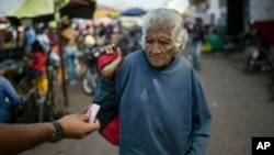 An elderly woman is offered cash as she begs at a wholesale food market in Caracas, Venezuela, Monday, Jan. 28, 2019. (AP Photo/Rodrigo Abd)