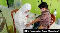 Petugas medis mengenakan APD mengambil sampel darah untuk pemeriksaan tes cepat salah satu anggota Panitia Pemungutan Suara di Puskesmas Kecamatan Lage, Kabupaten Poso, Sulawesi Tengah, 25 Juni 2020. (Foto: KPU Kabupaten Poso)