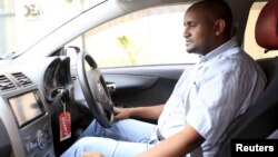 An Uber taxi driver sits in his car in Nairobi March 9, 2016.