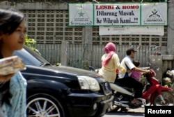 Pengendara motor melintas di depan spanduk bertuliskan penolakan terhadap kaum LGBT di kawasan Cigondewah Kaler, Bandung, Jawa Barat, 27 Januari 2016. (Foto: Reuters)