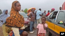 FILE- stranded people stand at a roadblock that separates Guinea and Sierra Leone.