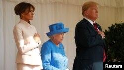 Prezidan Donald Trump ak Premyè Dam Lèzetazini an, Melania Trump, ki antoure Rèn Elizabeth II, ap koute Gad Coldstream yo pandan y ap jwe Im Nasyonal ameriken an pandan yon vizit nan Chato Windsor la, nan Windsor, Grand Bretay.