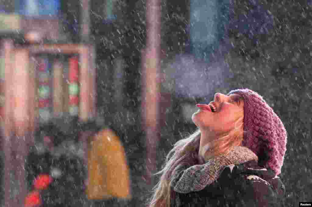 A tourist catches snowflakes on her tongue in Times Square, New York, Jan. 2, 2014.