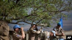 FILE - U.N. peacekeepers from the United Nations Disengagement Observer Force, also known as UNDOF, observe Syria's Quneitra province at an observation point on Mt. Bental in the Israeli-controlled Golan Heights, overlooking the border with Syria, Friday,