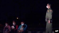 Агент пограничной охраны США задерживает группу нелегальных мигрантов на южной границе