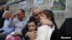 哈马斯领导人哈尼耶亲吻被以色列空袭打死的哈马斯军事指挥官贾巴里的儿子(2012年11月22日)