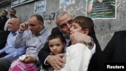 이스라엘-하마스간 휴전 체결 첫 날인 22일 가자지구에서 죽은 동료의 아들에 입맞추는 하마스 고위급 지도자.