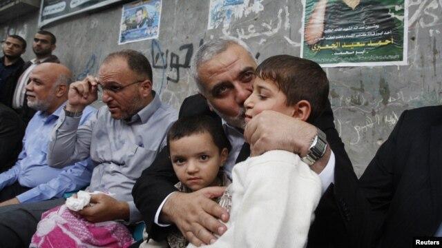 Pemimpin senior Hamas Ismael Haniyeh mencium anak kepala militer Hamas yang tewas dalam serangan udara Israel. (Foto: AP)