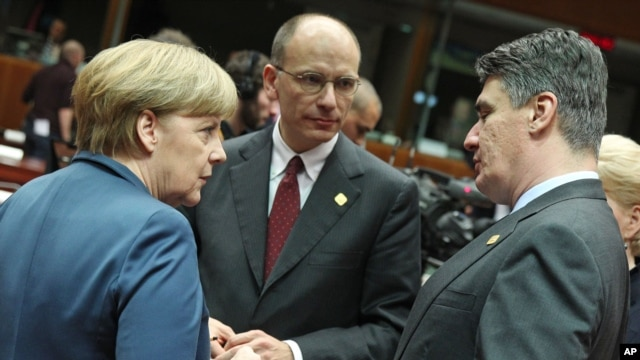 German Chancellor Angela Merkel, left, talks with Croatia's Prime Minister Zoran Milanovic, right, and Italy's Prime Minister Enrico Letta, during an EU summit at the European Council building in Brussels, Belgium, Dec. 19, 2013.
