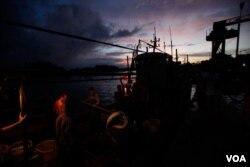 Para nelayan menurunkan ikan dari perahu mereka di sebuah desa nelayan di kota Tanmen, provinsi Hainan, di sebelah Laut China Selatan. (Foto: VOA)