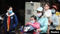Một gia đình tham gia giao thông bằng xe máy trên đường phố Hà Nội giữa đại dịch COVID. Mô hình chăm sóc sức khoẻ toàn dân của Việt Nam và quốc gia Cộng sản láng giềng được coi là một mô hình cho các quốc gia đang phát triển khác học tập.