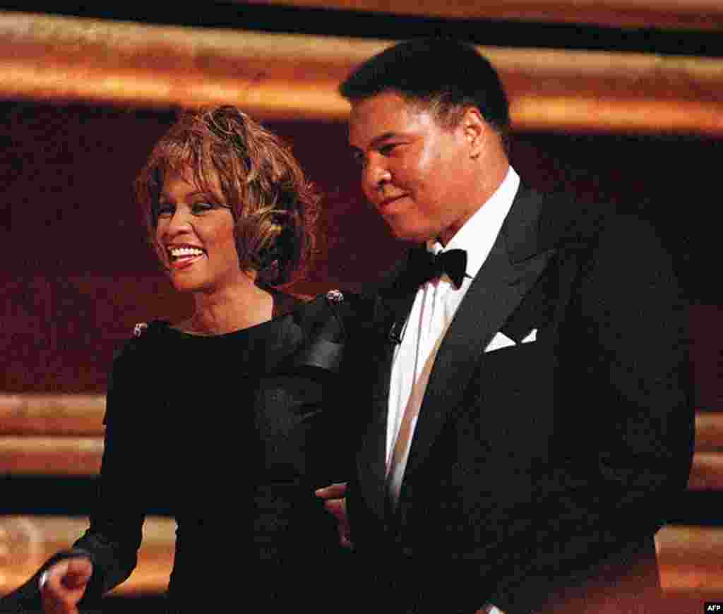 On October 21, 1998 former World Heavyweight Boxing Champion Muhammad Ali is greeted by singer Whitney Houston as he arrives on stage at New York's Radio City Music Hall. Houston died February 11, 2012. (AP)