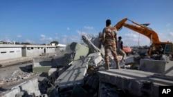 利比亚起义战士使用重型机械拆除的黎波里卡扎菲大院巴博•阿齐兹亚的一座警卫角楼。(2011年10月16日)