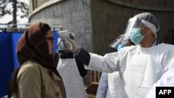 Petugas kesehatan memeriksa suhu badan seorang perempuan (foto: ilustrasi).