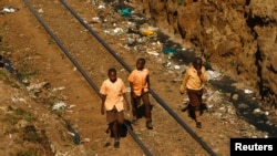 FILE - Children walk along a railway track passing through a deep trench in the Kibera slum of Kenya's capital Nairobi February 26, 2015.
