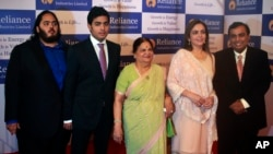 India's largest private sector company, Reliance Industries chairman Mukesh Ambani, right, poses or photographs with his wife Nita Ambani, second right, mother Kokilaben Ambani, center, sons Akash Ambani, second left and Anant Ambani, left during the company's annual general meeting in Mumbai, India.