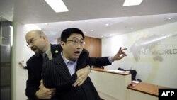 """Ông Ðỗ Kiến Quốc, một người biểu tình chống lại """"Báo cáo Trung Quốc năm 2030"""" của Ngân hàng Thế giới, bị nhân viên an ninh kéo ra khỏi phòng họp báo tại Bắc Kinh, ngày 28/2/2012"""