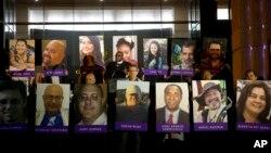 San Bernardino County employees hold up photos of the San Bernardino shooting victims during a candlelight vigil on Dec. 7, 2015, in San Bernardino, Calif.