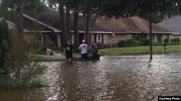 Three men prepare to kayak down their street to help out those in need, as well as find food and other supplies. (Photo courtesy of Abby TerHaar)