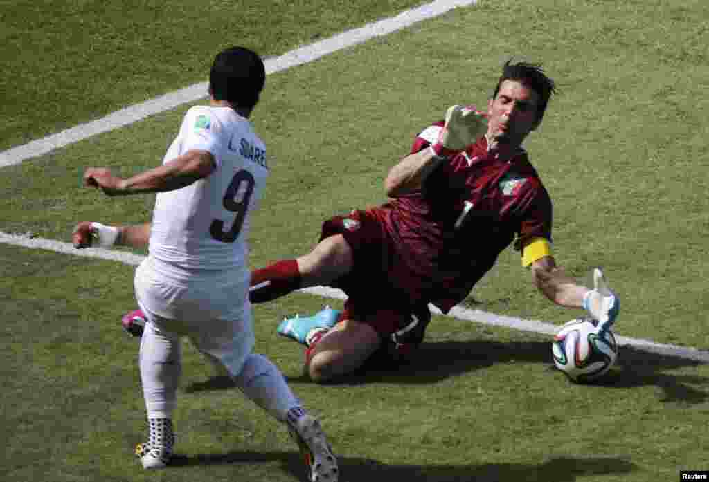 Italy's goalkeeper Gianluigi Buffon deflects a shot by Uruguay's Luis Suarez during their match at the Dunas arena in Natal, June 24, 2014.