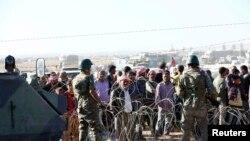 Tentara Turki bersiaga saat para pengungsi Kurdi dari Suriah menunggu di belakang sebuah pagar perbatasan dekat kota Suruc di sebelah tenggara provinsi Sanliurfa, Turki (22/9).
