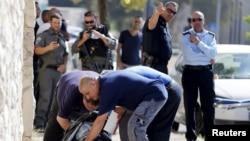 Cảnh sát Israel kiểm tra thi thể của 1 người đàn ông Palestine bị bắn chết sau khi định tấn công cảnh sát Israel, trên 1 con đường ở Jerusalem, 17/10/2015.