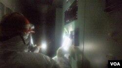 Seorang pekerja memeriksa alat pendeteksi tingkat radiasi di salah satu ruang di PLTN Fukushima, Jepang (23/3).