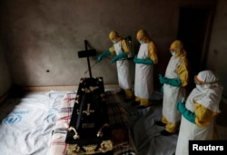 A healthcare worker sprays a room during a funeral of Kavugho Cindi Dorcas who is suspected of dying of Ebola in Beni, North Kivu Province of Democratic Republic of Congo, Dec. 9, 2018.