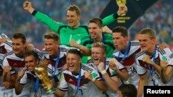 Para pemain Jerman berpose bersama Piala Dunia yang baru mereka raih di stadion Maracana, Rio de Janeiro, Minggu (13/7).
