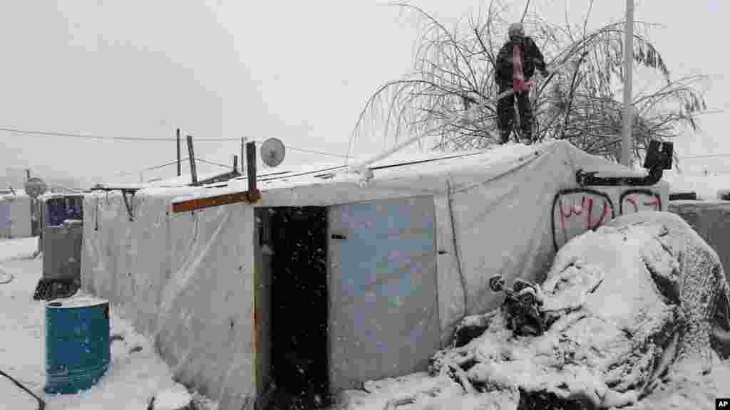 A Syrian man stands on top of his tent as he removes snow at a refugee camp in Deir Zannoun village, in the Bekaa valley, east Lebanon, Jan. 7, 2015.