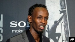 "Barkhad Abdi poses for photographers as he walks the red carpet at a screening for the movie ""Captain Phillips"" at the Newseum in Washington, Oct. 2, 2013."