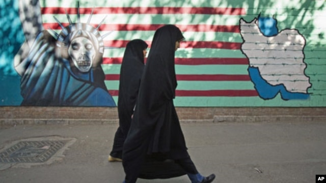 Iranian women walk past an anti-U.S. mural on the wall of the former U.S. embassy in Tehran, Iran, October 12, 2011.