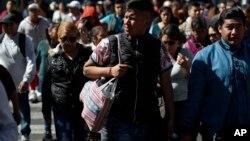 Seorang pria menggunakan tas kain untuk membawa belanjaannya di Mexico City, Rabu, 1 Januari 2020. (Foto: AP)