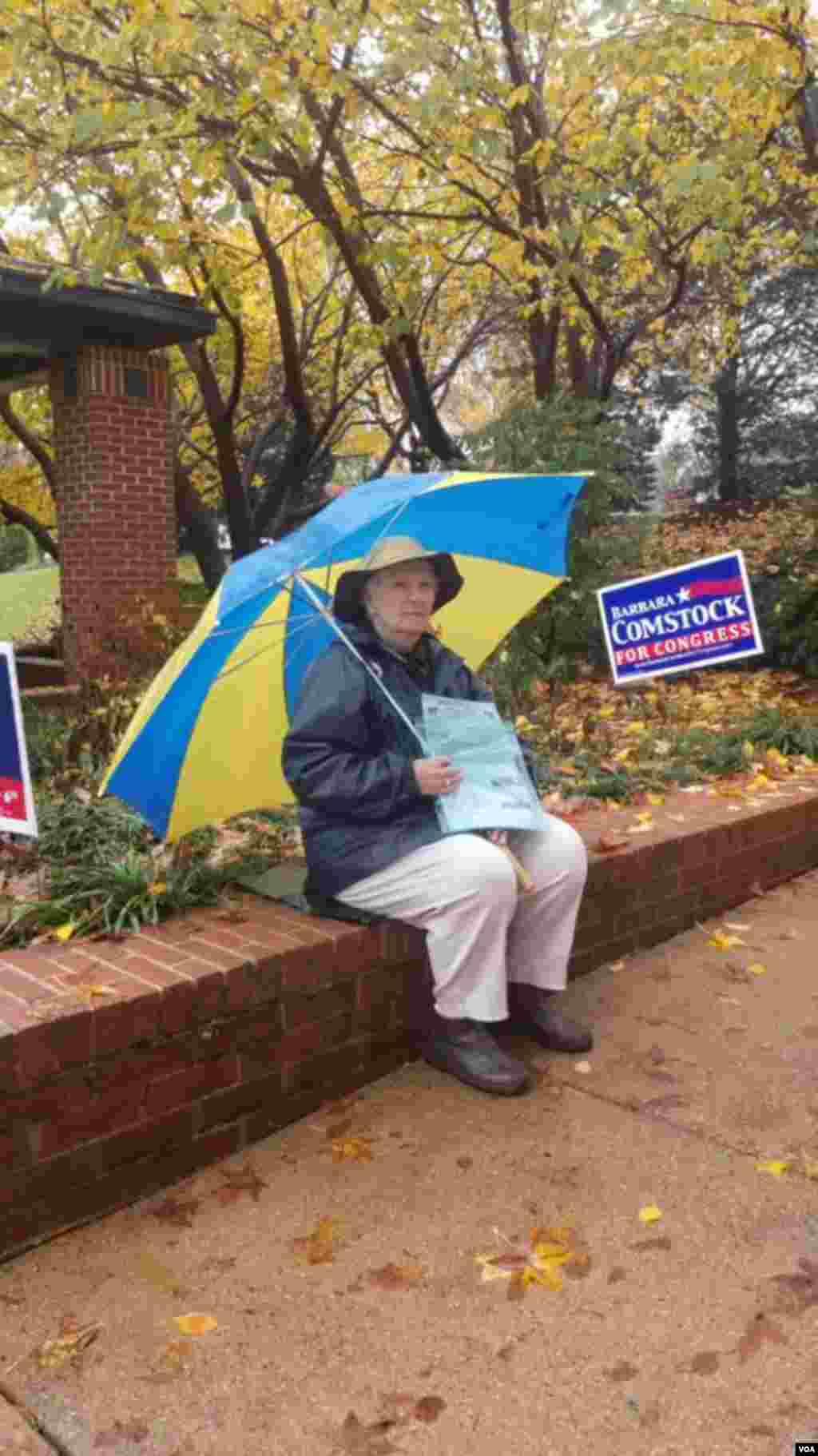 支持民主党的志愿者在雨中等待向选民分发民主党选票。 (美国之音魏之拍摄)
