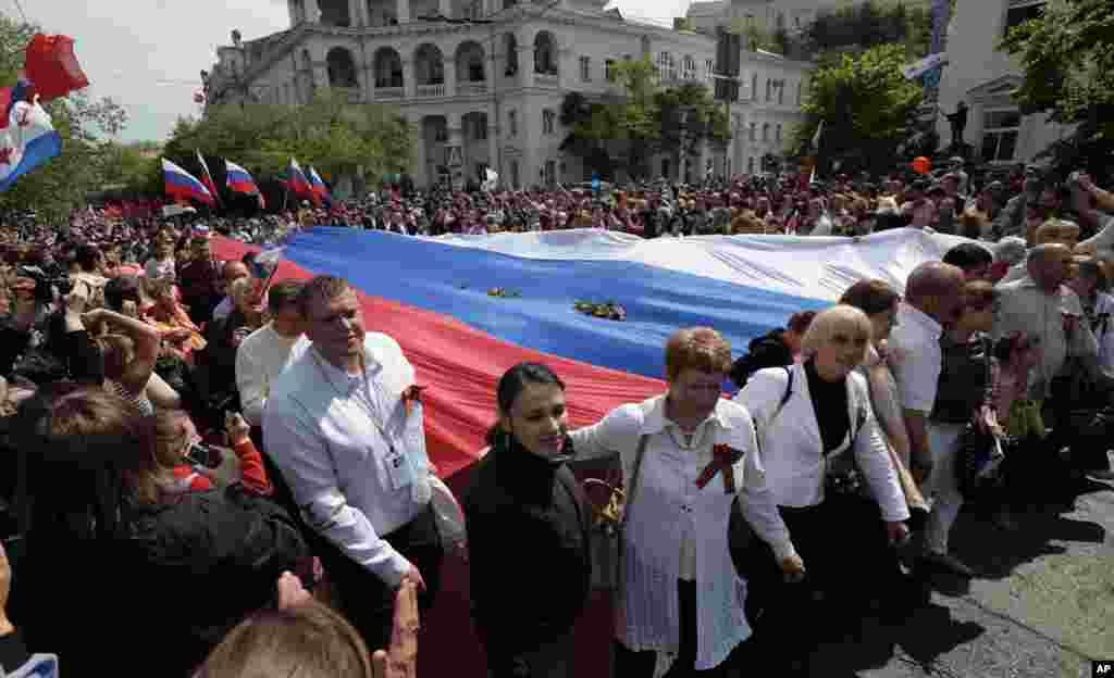 Local residents carry a giant Russian flag as they march through the city after the Victory Day military parade in Sevastopol, Crimea.