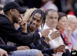 Artis rap Travis Scott, tengah, bereaksi selama pertandingan bola basket NBA antara Houston Rockets dan Denver Nuggets di Houston, 5 April 2017. (Foto: AP)