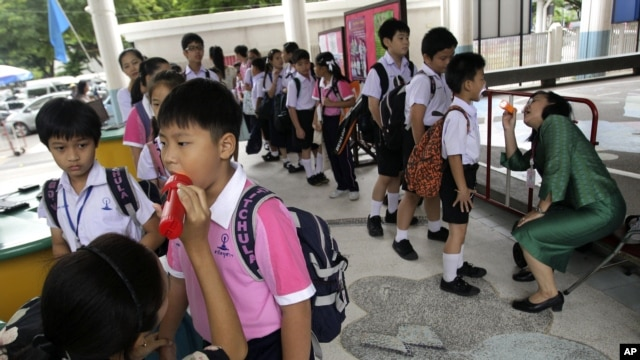 Thai teachers check the mouth of the students for hand, foot and mouth disease, before they get inside the school in Bangkok, July 25, 2012.