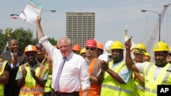 Illinois Governor Pat Quinn, surrounded by workers, holds up an approximately $1-billion capital spending plan intended to create jobs and help repair Illinois roads and bridges, during a signing ceremony in Chicago, July 22, 2014.