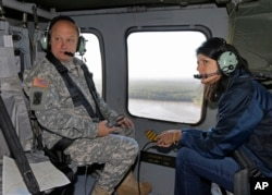 South Carolina Gov. Nikki Haley, right, and Major Gen. Bob Livingston, left, view flood damage from a helicopter in Columbia, S.C., Oct. 6, 2015.