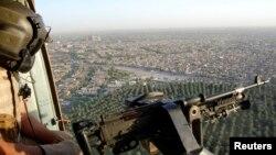 Anggota Angkatan Laut Irak memandang keluar dari helikopter militer di atas kota Baghdad.