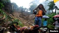 15일 멕시코 아카풀코시의 홍수 피해 현장 옆에 한 소년이 서있다.