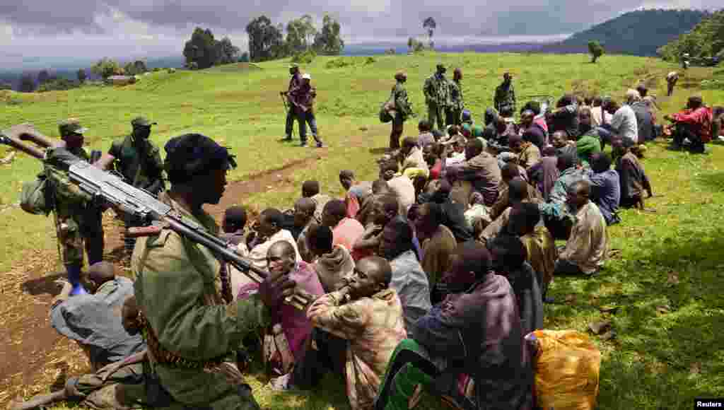 Congolese soldiers guard suspected M23 rebel fighters who surrendered in Chanzo village in the Rutshuru territory near the eastern town of Goma. Democratic Republic of Congo's M23 rebel group called an end to a 20-month revolt after the army captured its last hilltop stronghold, raising hopes for peace in a region where millions have died in nearly two decades of violence.