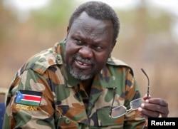 South Sudan's rebel leader Riek Machar speaks to rebel General Peter Gatdet Yaka (not seen) in a rebel controlled territory in Jonglei State, Feb. 1, 2014.